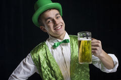 A man (Saint Patrick) smile in a green. Vest with a green hat and bow tie. He keeps a glass of beer in his hand. It is St. Patrick's Day Royalty Free Stock Images