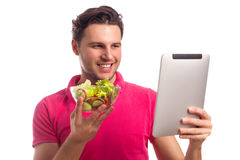 Man With Salad Looking At The Computer Tablet On White Backgroun Stock Images