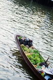 Man sales on the boat. The man paddle boats sell fruit in the market Stock Images