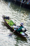 Man sales on the boat. The man paddle boats sell fruit in the market Stock Photography