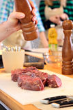 Man is salting a meat Royalty Free Stock Image