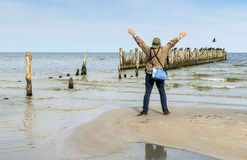 Man saluting birds sitting on old broken pier Royalty Free Stock Photo