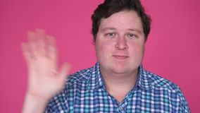 Man saluting, greeting, waving hand, isolated on pink background. Man saluting, greeting, waving hand, isolated on pink background stock footage