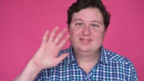Man saluting, greeting, waving hand, isolated on pink background. Man saluting, greeting, waving hand, isolated on pink background, slow motion stock video
