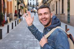 Man saluting someone he knows outdoors.  stock image