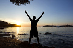 Man saluting sun at sea Royalty Free Stock Images