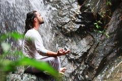 Man sammanträde i meditationyoga vaggar på på vattenfallet i tropiskt Arkivfoto