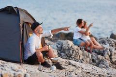 Man sammanträde på den steniga stranden som ser solnedgången, frun och dottern som nära sitter fotografering för bildbyråer