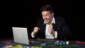 Man sammanträde på en bärbar dator och att spela på online-kasino close upp lager videofilmer