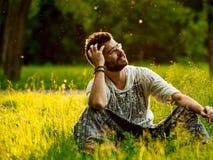 Man sammanträde på ett gräs i parkera, att le som är drömlikt Royaltyfri Fotografi
