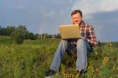 Man sammanträde på gräset med en bärbar dator Fotografering för Bildbyråer