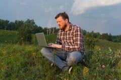 Man sammanträde på gräset med en bärbar dator på hans knä Arkivbilder