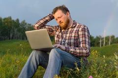 Man sammanträde på gräset med en bärbar dator på hans knä Arkivbild