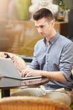 Man sammanträde på kafét med bärbara datorn och mobiltelefonen arkivfoto