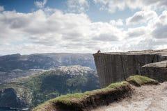 Man sammanträde på Preikestolenen, predikstol vaggar i härligt Norge berglandskap royaltyfria bilder