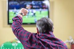 Man sammanträde på soffabifall på leken på TV royaltyfri fotografi