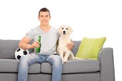 Man sammanträde på soffan med hans valp och fotboll Arkivbild