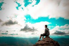Man sammanträde vaggar på överst av berget som ser till himmel royaltyfri bild