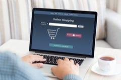 Man sammanträde på en dator och gör online-shopping Royaltyfri Bild