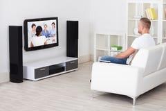 Man sammanträde på en soffa i hans hållande ögonen på television för vardagsrum Royaltyfria Bilder