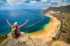 Man sammanträde på kanten av en klippa som tycker om sikt av Playa de La Arkivfoton