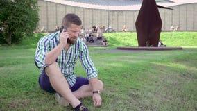 Man samtal av smartphonen som sitter på gräs steadicam stock video