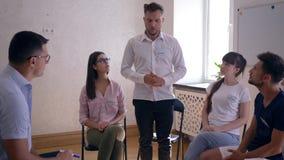 Man samtal och att dela av sinnesrörelser under anseende för terapiperiod i cirkel av folk stock video