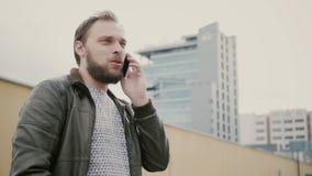 Man samtal på telefonanseendet på taket, då går bort räcker closeupen 4K Arkivfoton