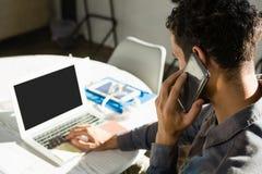 Man samtal på telefonen, medan genom att använda bärbara datorn i regeringsställning royaltyfria foton