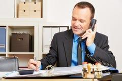 Man samtal till heta linjen för kundservice på telefonen Royaltyfri Fotografi