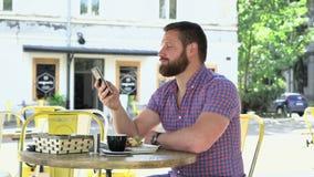 Man samtal vid smartphonen under frukosten, shower ok till cameaen arkivfilmer
