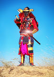 Man in samurai costume pulls out his powerfull hot sword. Royalty Free Stock Photos