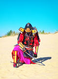 Man in samurai costume with sword. Samurai in ancient armor in a field with sword. Original Character Stock Photo