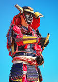 Man in samurai costume with sword on blue sky background. Royalty Free Stock Images