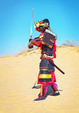 Man in samurai costume with sword running on the sand. Royalty Free Stock Images