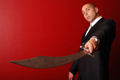 Man with Samurai sword. Man in business suit against a red background holding a samurai sword out towards the camera. Focus is on the detailed pattern on the Stock Images