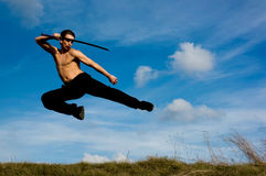 Man samurai sword sky. Young handsome man with samurai sword jumping against blue sky Royalty Free Stock Images