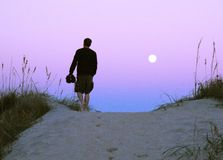 Man on sand dunes at twilight Stock Photos