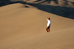 Man in sand observing Stock Image