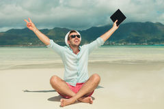Man in sand showing victory sign and holding an ipad. Man sitting in sand with legs crossed showing victory sign and holding an ipad in hand, celebrating success Royalty Free Stock Image