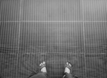 Man in sandals standing on metal grid background. Horizontal orientation vivid vibrant spacedrone808 bright black white rich composition design concept element stock images