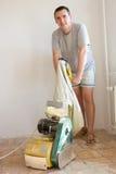 Man Sanding Floor. Cheerful man sanding (scraping) floor Royalty Free Stock Photo