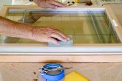 Man Sanding Window Frame. Wood on workbench Stock Photo