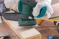 Man sanding a wood with orbital sander Royalty Free Stock Photos