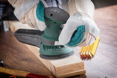 Man sanding a wood with orbital sander Stock Photography