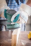 Man sanding a wood with orbital sander Royalty Free Stock Photo