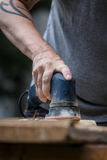 Man is sanding a wooden plank Royalty Free Stock Image
