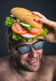 Man with sandwich on his head Stock Photo