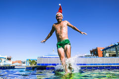 A man in a Santa Claus Cap jumps into a pool at a tropical resort. In sunny day royalty free stock image