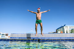 A man in a Santa Claus Cap jumps into a pool at a tropical resort. In sunny day royalty free stock photography